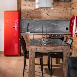 Immagine di una cucina stile rurale di medie dimensioni con lavello da incasso, ante lisce, ante beige, paraspruzzi grigio, parquet chiaro, nessuna isola, pavimento beige e top grigio