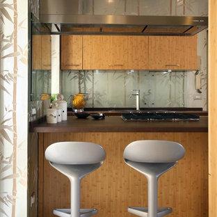 Esempio di una cucina ad U tropicale di medie dimensioni con ante lisce, ante in legno scuro, paraspruzzi multicolore, paraspruzzi con lastra di vetro, penisola e pavimento beige