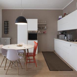 Einzeilige, Mittelgroße Moderne Wohnküche ohne Insel mit Waschbecken, flächenbündigen Schrankfronten, weißen Schränken, Laminat-Arbeitsplatte, Küchenrückwand in Metallic, Küchengeräten aus Edelstahl und braunem Holzboden in Turin