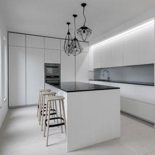 Idee per una cucina a L minimalista con ante lisce, ante bianche, paraspruzzi grigio, isola e pavimento bianco