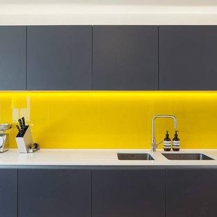 他の地域の中サイズのモダンスタイルのおしゃれなキッチン (アンダーカウンターシンク、インセット扉のキャビネット、黒いキャビネット、クオーツストーンカウンター、黄色いキッチンパネル、カラー調理設備、黒いキッチンカウンター) の写真