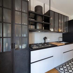 Esempio di una cucina contemporanea con lavello sottopiano, ante lisce, ante bianche, paraspruzzi grigio, elettrodomestici in acciaio inossidabile, pavimento in legno massello medio e top nero