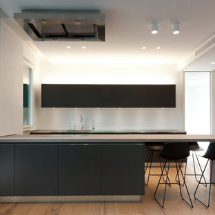 Idee per una cucina moderna con top in acciaio inossidabile, ante lisce, ante nere, una penisola, elettrodomestici neri, parquet chiaro e pavimento beige