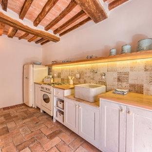 Idee per una piccola cucina lineare mediterranea chiusa con lavello stile country, ante in stile shaker, ante bianche, top in legno, paraspruzzi beige, paraspruzzi con piastrelle in ceramica, pavimento in terracotta e nessuna isola