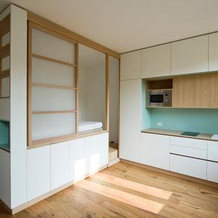 Esempio di una piccola cucina nordica con parquet chiaro, lavello da incasso, ante lisce, ante bianche, paraspruzzi verde, elettrodomestici in acciaio inossidabile, nessuna isola e top beige