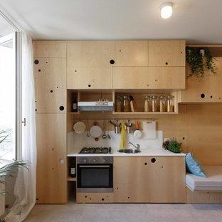Immagine di una piccola cucina minimal con lavello sottopiano, ante lisce, ante in legno scuro, paraspruzzi bianco, elettrodomestici in acciaio inossidabile e nessuna isola
