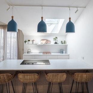 Idee per una cucina costiera di medie dimensioni con ante lisce, ante in legno chiaro, top in quarzo composito, paraspruzzi bianco, elettrodomestici neri, pavimento in legno massello medio e top bianco