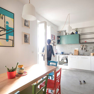 Foto di una cucina abitabile boho chic con ante lisce, ante bianche, paraspruzzi grigio, pavimento in cemento e pavimento grigio