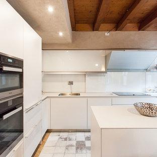 Immagine di una grande cucina contemporanea con lavello sottopiano, ante lisce, ante bianche, top in superficie solida, paraspruzzi bianco, elettrodomestici neri e un'isola