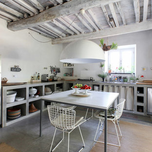 This is an example of a mediterranean l-shaped eat-in kitchen in Milan with a drop-in sink, open cabinets, grey cabinets, concrete benchtops, white splashback, stainless steel appliances, concrete floors, no island, grey floor and grey benchtop.
