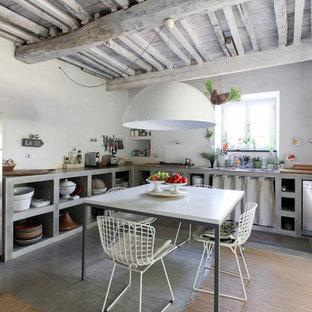 Mediterrane Wohnküche ohne Insel in L-Form mit Einbauwaschbecken, offenen Schränken, grauen Schränken, Betonarbeitsplatte, Küchenrückwand in Weiß, Küchengeräten aus Edelstahl, Betonboden, grauem Boden und grauer Arbeitsplatte in Mailand