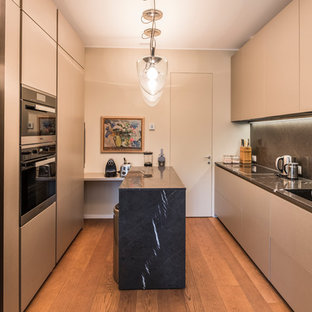 Inspiration for a small contemporary u-shaped separate kitchen in Milan with an integrated sink, beaded inset cabinets, beige cabinets, wood benchtops, black splashback, marble splashback, black appliances, light hardwood floors, with island, yellow floor and black benchtop.