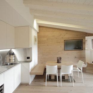 Einzeilige, Mittelgroße Moderne Wohnküche mit Einbauwaschbecken, flächenbündigen Schrankfronten, weißen Schränken, Edelstahl-Arbeitsplatte, Küchenrückwand in Metallic, Küchengeräten aus Edelstahl und hellem Holzboden in Venedig