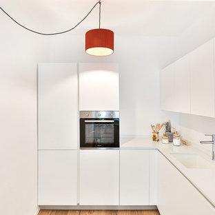 Foto di una piccola cucina a L minimal con lavello sottopiano, ante lisce, ante bianche, top in superficie solida, paraspruzzi bianco, elettrodomestici in acciaio inossidabile e pavimento in legno massello medio