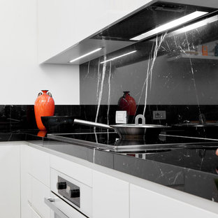 Design ideas for a large contemporary kitchen in Milan with an integrated sink, flat-panel cabinets, white cabinets, marble benchtops, black splashback, stone slab splashback, white appliances and marble floors.