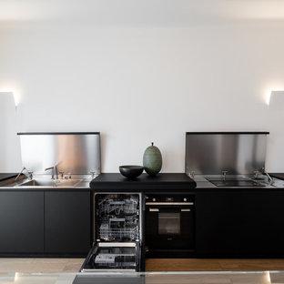 Ispirazione per una cucina moderna con lavello a vasca singola, ante nere, top in acciaio inossidabile, elettrodomestici in acciaio inossidabile, parquet chiaro, nessuna isola, pavimento marrone e top nero