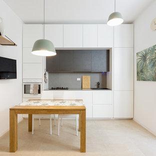 Esempio di una piccola cucina minimal con ante lisce, ante bianche, paraspruzzi grigio, nessuna isola, lavello da incasso, elettrodomestici da incasso e pavimento beige