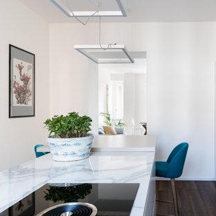 Esempio di una cucina parallela design di medie dimensioni con ante lisce, top in superficie solida, parquet scuro, isola, top bianco, ante bianche, elettrodomestici da incasso e pavimento marrone