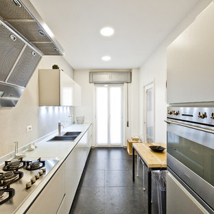 Mid-sized contemporary single-wall eat-in kitchen in Rome with a double-bowl sink, flat-panel cabinets, white cabinets, solid surface benchtops, stainless steel appliances and slate floors.