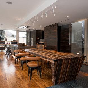 Foto di una grande cucina minimal con ante lisce, ante marroni, pavimento in legno massello medio, 2 o più isole, lavello integrato, elettrodomestici in acciaio inossidabile e pavimento marrone