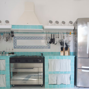 Mid-sized beach style l-shaped separate kitchen in Rome with a drop-in sink, open cabinets, turquoise cabinets, tile benchtops, green splashback, ceramic splashback, stainless steel appliances, ceramic floors, no island and turquoise floor.