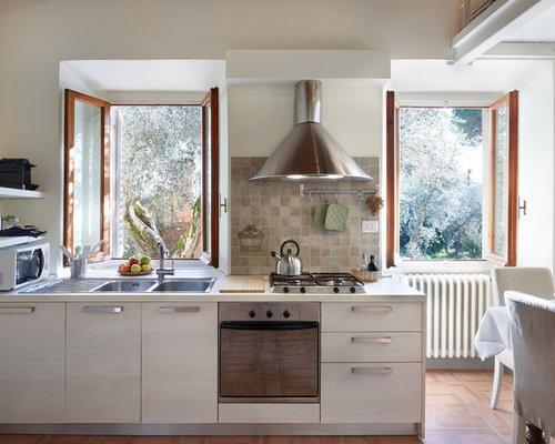 Cucina con ante in legno chiaro e pavimento in terracotta foto e