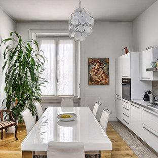 Esempio di una cucina abitabile design con ante lisce, ante bianche, paraspruzzi grigio, parquet chiaro e top bianco
