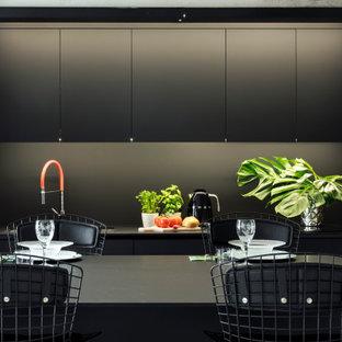 Esempio di una piccola cucina contemporanea con ante lisce, ante nere, paraspruzzi nero, elettrodomestici da incasso, nessuna isola e top nero