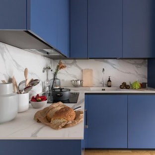 Small contemporary l-shaped kitchen in Milan with an integrated sink, flat-panel cabinets, blue cabinets, grey splashback, panelled appliances, beige floor and grey benchtop.
