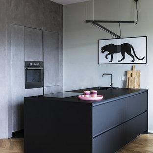 Idee per una cucina parallela design con ante nere, elettrodomestici in acciaio inossidabile, top nero, lavello da incasso, ante lisce, parquet chiaro, penisola e pavimento marrone