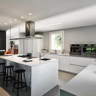 Immagine di una cucina a L minimal con ante lisce, ante bianche, elettrodomestici in acciaio inossidabile, isola, top bianco, lavello sottopiano, paraspruzzi grigio, pavimento in cemento e pavimento grigio