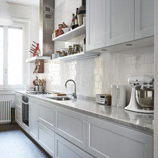 Immagine di una cucina lineare tradizionale di medie dimensioni con lavello sottopiano, ante in stile shaker, ante bianche, paraspruzzi bianco, paraspruzzi con piastrelle diamantate, elettrodomestici in acciaio inossidabile, pavimento multicolore e top grigio