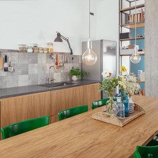 Idee per una cucina abitabile industriale con pavimento in gres porcellanato, pavimento grigio, lavello sottopiano, ante lisce, ante in legno chiaro, paraspruzzi multicolore e top grigio