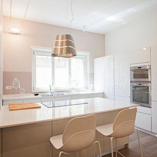Ispirazione per una cucina contemporanea di medie dimensioni con lavello da incasso, ante lisce, ante bianche, top in superficie solida, elettrodomestici in acciaio inossidabile, pavimento in legno massello medio e penisola