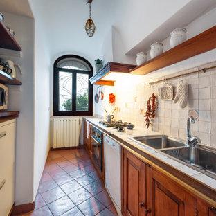 ナポリの小さい地中海スタイルのおしゃれなキッチン (ダブルシンク、落し込みパネル扉のキャビネット、中間色木目調キャビネット、タイルカウンター、白いキッチンパネル、磁器タイルのキッチンパネル、白い調理設備、テラコッタタイルの床、茶色い床、白いキッチンカウンター、三角天井) の写真