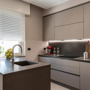 Immagine di una piccola cucina parallela contemporanea con lavello sottopiano, ante lisce, ante grigie, paraspruzzi grigio, paraspruzzi in lastra di pietra, penisola e top grigio