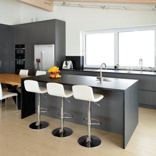 Idee per un grande cucina con isola centrale contemporaneo con ante lisce, ante grigie, top in granito, paraspruzzi nero, paraspruzzi in granito, top nero, travi a vista, lavello a vasca singola e pavimento beige
