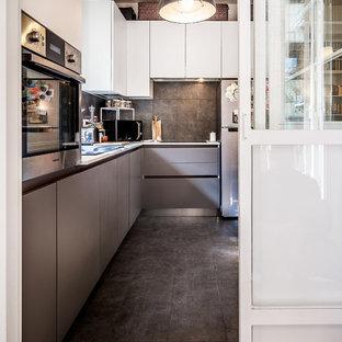 Immagine di una grande cucina a L contemporanea chiusa con ante lisce, ante grigie, pavimento nero, paraspruzzi nero, elettrodomestici in acciaio inossidabile e top grigio