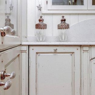 他の地域のシャビーシック調のおしゃれなキッチン (一体型シンク、インセット扉のキャビネット、ヴィンテージ仕上げキャビネット、大理石カウンター、白いキッチンパネル、石スラブのキッチンパネル) の写真