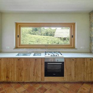 Modelo de cocina lineal, rústica, de tamaño medio, con fregadero bajoencimera, armarios con paneles lisos, puertas de armario de madera clara, encimera de cemento, electrodomésticos de acero inoxidable y suelo de baldosas de terracota
