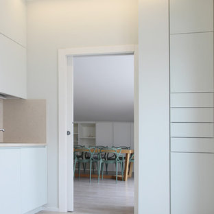 Photo of a contemporary l-shaped separate kitchen in Other with a drop-in sink, beaded inset cabinets, green cabinets, granite benchtops, beige splashback, stone slab splashback, black appliances, linoleum floors, grey floor and beige benchtop.