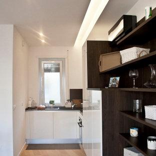 Modelo de cocina actual, pequeña, abierta, con fregadero encastrado, encimera de granito, electrodomésticos de acero inoxidable, suelo de madera clara y encimeras grises