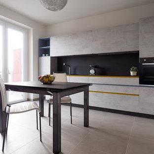 Inredning av ett modernt mellanstort svart svart kök, med en undermonterad diskho, släta luckor, grå skåp, kaklad bänkskiva, svart stänkskydd, stänkskydd i porslinskakel, rostfria vitvaror, klinkergolv i keramik och grått golv
