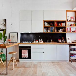 Idee per una cucina nordica di medie dimensioni con lavello integrato, ante lisce, ante bianche, top in legno, paraspruzzi nero, paraspruzzi con piastrelle in pietra, elettrodomestici neri, parquet chiaro, isola e pavimento beige