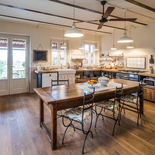 This is an example of a large country l-shaped open plan kitchen in Turin with a farmhouse sink, open cabinets, black cabinets, wood benchtops, beige splashback, white appliances, medium hardwood floors and no island.