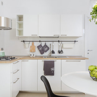 Eat-in kitchen - small scandinavian l-shaped beige floor eat-in kitchen idea in Rome with flat-panel cabinets, white cabinets, wood countertops, white backsplash, no island and a drop-in sink