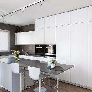 Esempio di una cucina a L moderna di medie dimensioni con lavello a doppia vasca, ante lisce, ante bianche, top in quarzo composito, elettrodomestici neri, isola, top grigio, pavimento in legno massello medio e pavimento marrone