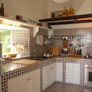 Diseño de cocina ecléctica, sin isla, con fregadero de doble seno, armarios con puertas mallorquinas, puertas de armario blancas, encimera de azulejos, salpicadero multicolor, salpicadero con mosaicos de azulejos, electrodomésticos de acero inoxidable y suelo de baldosas de cerámica
