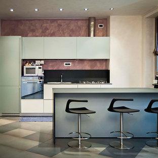 Modelo de cocina lineal, contemporánea, grande, abierta, con fregadero de doble seno, puertas de armario grises, encimera de vidrio, salpicadero negro, salpicadero de azulejos de vidrio, electrodomésticos de acero inoxidable, suelo de baldosas de porcelana, una isla y suelo gris