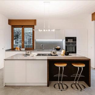 Idee per una grande cucina design con lavello sottopiano, ante lisce, ante bianche, paraspruzzi grigio, elettrodomestici da incasso, pavimento grigio e top grigio